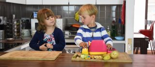 Two young children playing with food in a kitchen