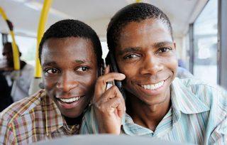 Two smiling men talking on mobile phones