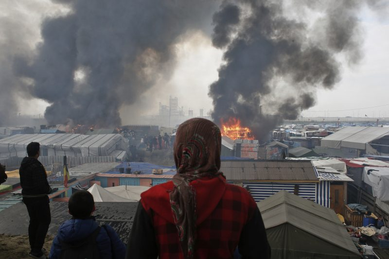 People stand and watch migrant camp Calais on fire.