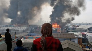 Migrant watching fires in Calais camp