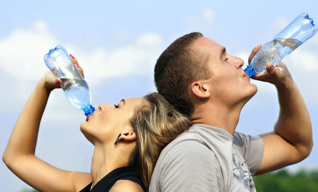 Two people drinking bottles of water