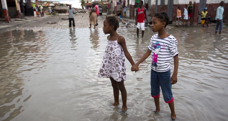 Two young girls stand holding hands in a flooded street