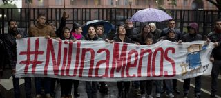 People hold a banner that reads in Spanish