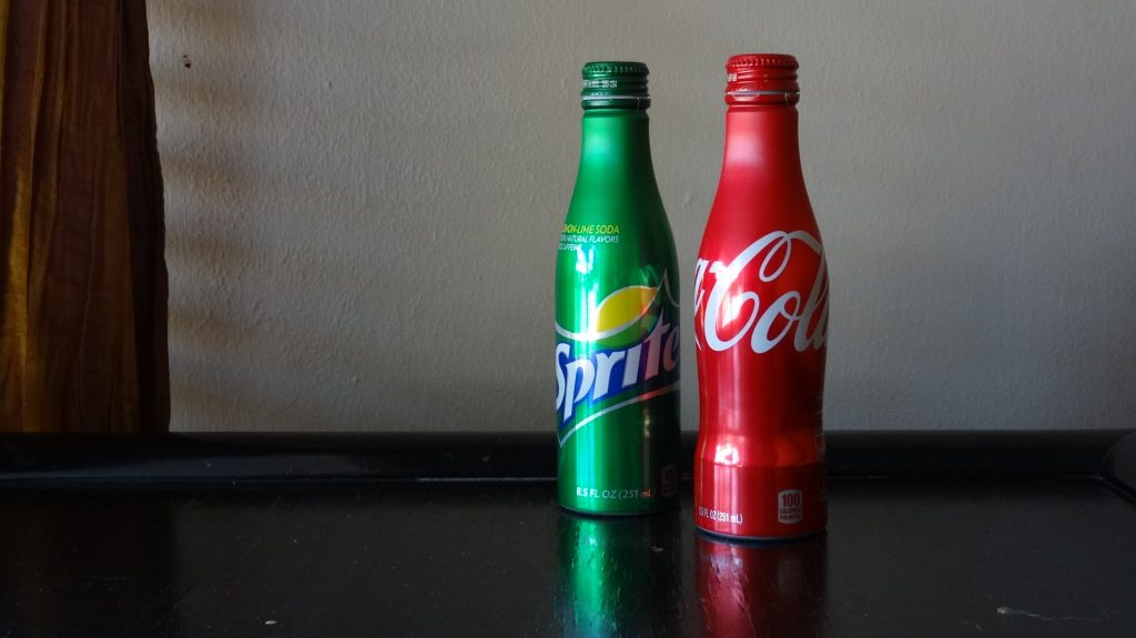 A bottle of Sprite and a bottle of Coca Cola