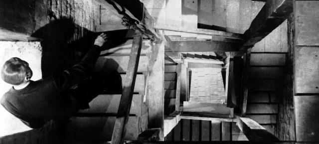 A still from Vertigo - James Stewart walks on stairs