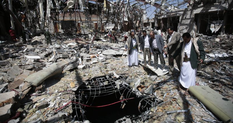 Members of Higher Council for Civilian Community Organization, inspect a destroyed funeral hall as they protest against a deadly Saudi-led airstrike on a funeral hall six days ago, in Sanaa, Yemen
