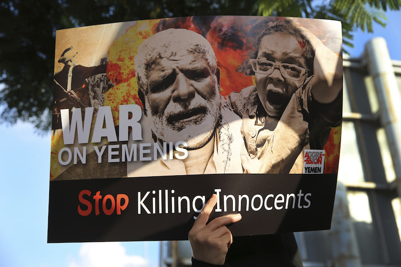A person holds up a protest poster against the war in Yemen