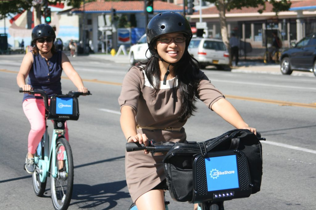 Two girls ride city bikes in San Jose.