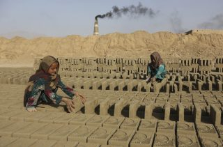 Afghan girls work in a brick factory