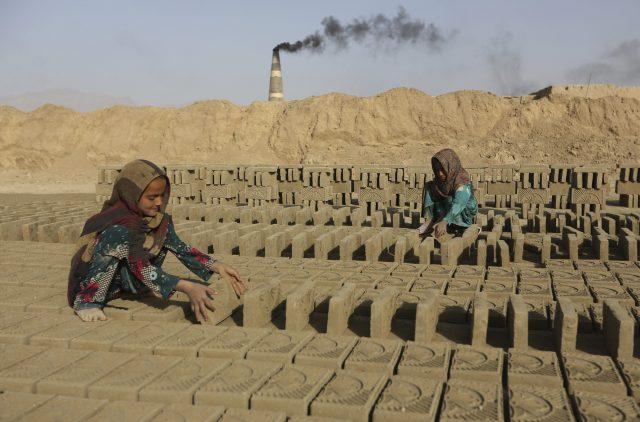 Afghan girls work in a brick factory