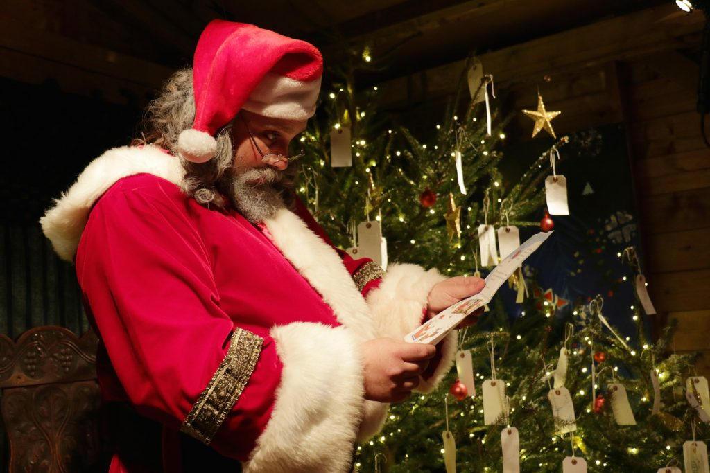 Santa Claus reading letters in his grotto.
