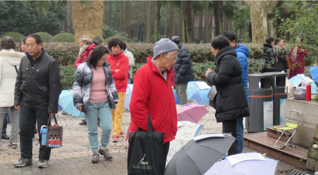 Parent inspects umbrellas at Shanghai marriage market.