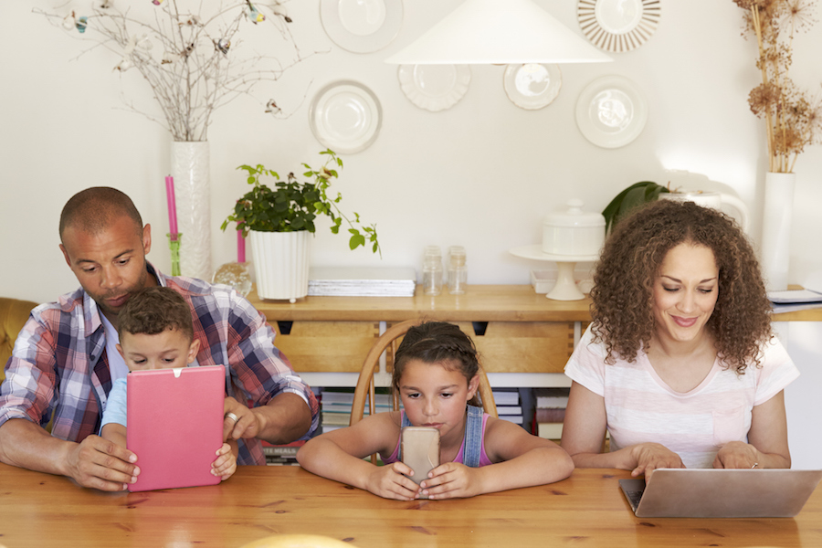 Family Sitting Around Table At Home Using Technology
