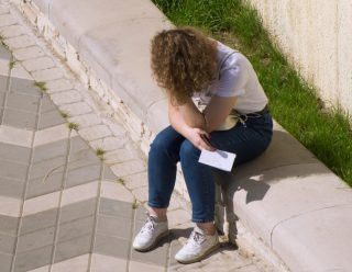 a-distressed-girl-sits-on-the-parapet-holding-a-letter-in-her-hands-holding-a-paper-and-experiencing_t20_Enx2oQ (1)