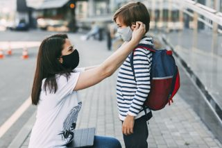mother-adjusts-her-sons-mask-a-mother-and-child-on-their-way-to-school-or-kindergarten-during-a_t20_ynp9e0