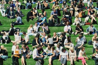 students-and-friends-chatting-and-laughing-as-they-gather-for-their-lunch-break-on-a-grassy-hill-in_t20_oEV6jk