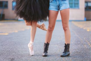 two-dancers-standing-in-a-parking-lot-one-dressed-in-a-black-tutu-and-her-pointe-shoes-the-other_t20_OzQXem