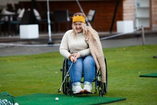 a-girl-in-a-wheelchair-plays-golf-woman-laughs-and-holds-a-golf-club_t20_lL9WZb