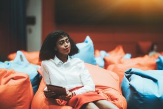 portrait-of-a-young-beautiful-african-american-businesswoman-sitting-on-an-orange-cushion-with-a_t20_xXK028