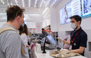 a-masked-and-gloved-cashier-serves-a-customer-in-a-medical-mask-job-h-m-supply-chain-management_t20_xXOkbX