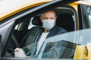 bald-man-taxi-driver-in-medical-face-mask-inside-yellow-car-looks-at-camera-concept-of-coronavirus_t20_R01yda