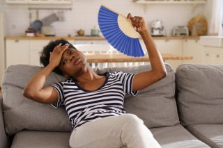 tired-african-american-woman-suffering-from-heatstroke-flat-without-air-conditioner-waving-blue-fan_t20_OJV2JE