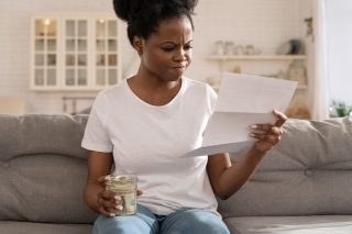 depressed-sad-black-girl-holding-last-cash-money-and-papers-calculate-domestic-bills-at-home-african_t20_9kY8O6