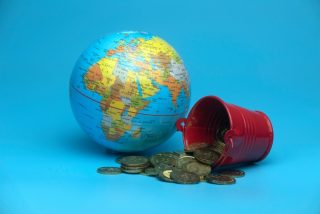 selective-focus-of-world-globe-and-a-red-bucket-with-a-gold-coins-isolated-on-a-blue-background_t20_2Wwl06