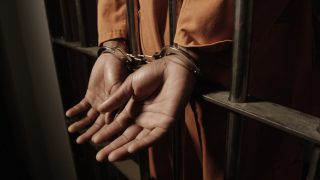 african-man-handcuffed-through-the-bars-of-a-prison-cell_t20_XQ30QR