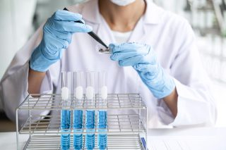 scientist-or-medical-in-lab-testing-sample-trial-with-reagent-mixing-reagents-in-glass-flask_t20_G0dr9m